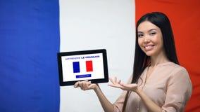 De tablet van de dameholding met leert Franse app, de vlag van Frankrijk op achtergrond, onderwijs stock footage