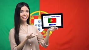 De tablet van de dameholding met leert Portugese app, vlag op achtergrond, onderwijs stock videobeelden