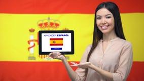 De tablet van de dameholding met leert Spaanse app, de vlag van Spanje op achtergrond, onderwijs stock videobeelden