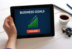 De tablet van de handholding met bedrijfsdoelstellingen concept op het scherm Stock Foto