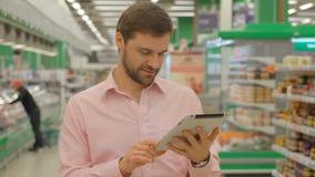 De tablet van de mensenholding in hypermarket opslag stock videobeelden