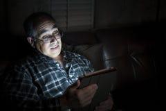 De tablet van de mensenlezing bij nacht Stock Afbeeldingen