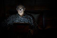 De tablet van de mensenlezing bij nacht Stock Foto