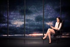 De tablet van de onderneemsterholding in bureauruimte met grafiekgrafieken  stock afbeeldingen