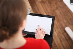 De tablet van de vrouwenholding in handen Hij drukt zijn vinger op de vertoning Royalty-vrije Stock Afbeelding