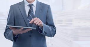 De tablet van de zakenmanholding in helder pakhuis stock foto's