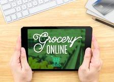 De tablet van de handholding met kruidenierswinkel online woord op houten lijst, Winkel Royalty-vrije Stock Foto's
