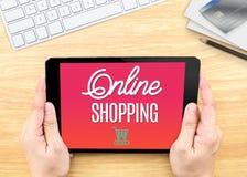 De tablet van de handholding met Online het winkelen woord op houten lijst, Int. Royalty-vrije Stock Foto's