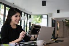 De tablet van het onderneemstergebruik op het werk jonge vrouw die werken op Stock Foto's