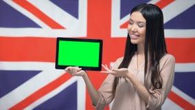 De tablet van de meisjesholding met het groene scherm, Britse vlag op achtergrond, migratie stock footage