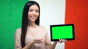De tablet van de meisjesholding met het groene scherm, Italiaanse vlag op achtergrond, migratie stock videobeelden