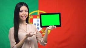 De tablet van de meisjesholding met het groene scherm, Portugese vlag op achtergrond, migratie stock footage