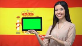 De tablet van de meisjesholding met het groene scherm, Spaanse vlag op achtergrond, migratie stock video