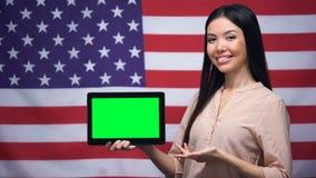De tablet van de meisjesholding met het groene scherm, de V.S. markeert op achtergrond, migratie stock footage
