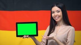 De tablet van de meisjesholding met het groene scherm, de vlag van Duitsland op achtergrond, migratie stock video