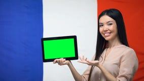 De tablet van de meisjesholding met het groene scherm, de vlag van Frankrijk op achtergrond, migratie stock videobeelden