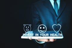 De tablet van de mensenholding Investeer in uw gezondheid stock afbeelding