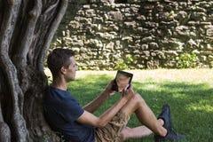 De tablet van de mensenlezing en geniet van rust in een park onder boom royalty-vrije stock foto's