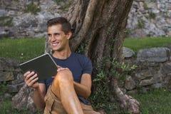 De tablet van de mensenlezing en geniet van rust in een park onder boom stock afbeelding
