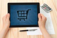 De tabletpc van de handengreep met boodschappenwagentje stock afbeeldingen