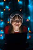 De Tabletpc van de meisjesholding in Kerstman` s Hoed Royalty-vrije Stock Fotografie