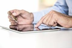 De tabletpc van de mensenholding en creditcard binnen, online Winkelend Stock Foto