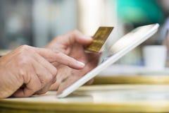 De tabletpc van de mensenholding en creditcard op koffieterras, het Winkelen Stock Foto's