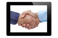 De tabletpc van het zakenliedenhandenschudden stock fotografie