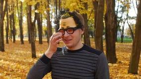 De tak raakte het oog van de ontevreden mens in een masker in het de herfstpark Grappig ogenblik stock videobeelden