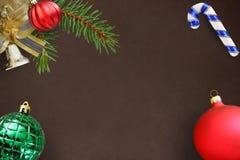 De tak van de Kerstmisspar, rode golvende saaie, groene geribbelde bal, klok en stok op donkere achtergrond Royalty-vrije Stock Fotografie