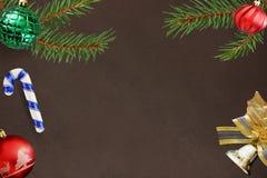 De tak van de Kerstmisspar, stok, rode golvende en groene geribbelde bal, klokdecoratie op donkere achtergrond Royalty-vrije Stock Foto