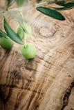 De tak van de olijf op olijf houten achtergrond Royalty-vrije Stock Afbeelding