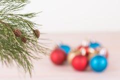 De tak van de pijnboomboom met de rode, blauwe en gouden achtergrond van Kerstmissnuisterijen Stock Afbeeldingen