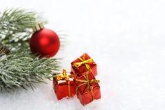 De tak van de suikerglazuurpijnboom met rode matte Kerstmisbal en drie doos van de Kerstmis de rode gift met gele boog op sneeuw Stock Foto's