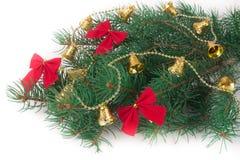 De tak van Kerstboom met korte die naalden verfraaide klokken en bogen op witte achtergrond worden geïsoleerd Stock Fotografie