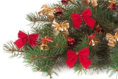 De tak van Kerstboom met korte die naalden verfraaide klokken en bogen op witte achtergrond worden geïsoleerd Stock Foto