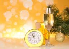 De tak van de Kerstmispijnboom met stuk speelgoed, glas champagne, gift en klok op gele achtergrond Stock Fotografie