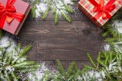 De takken van de Kerstmisspar op een donkere houten raad met sneeuw en gift-dozen Kerstmis of nieuw jaarkader voor uw project met stock afbeeldingen