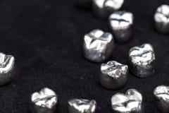 De tand zilveren kronen van de metaaltand op donkere zwarte oppervlakte Stock Afbeeldingen