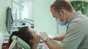 De tandarts behandelt tand stock video