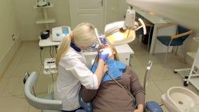 De tandarts behandelt tanden van jonge vrouw in de kliniek stock video