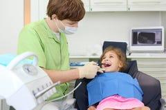 De tandarts behandelt tanden van meisje liggend als voorzitter royalty-vrije stock afbeelding
