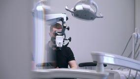 De tandarts doet een chirurgie in moderne kliniek stock footage