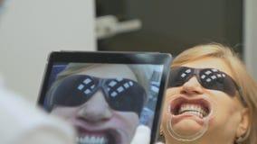 De tandarts in een speciaal die computerprogramma in de tablet wordt geladen controleert en regelt beet Geeft foto met een tablet stock videobeelden