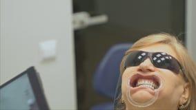 De tandarts in een speciaal die computerprogramma in de tablet wordt geladen controleert en regelt beet Geeft foto met een tablet stock footage