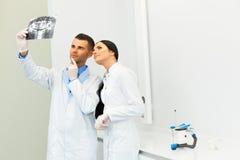 De tandarts en de vrouwelijke medewerker bespreken tandröntgenstraalbeeld royalty-vrije stock foto's