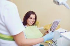 De tandarts en de patiënt bekijken röntgenstraal royalty-vrije stock afbeelding