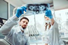 De tandarts en zijn medewerker spreken over het dossier van de patiënt Selectieve nadruk stock foto