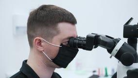 De tandarts gebruikt een microscoop voor het werk stock videobeelden