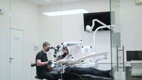 De tandarts gebruikt technologisch materiaal in kliniek stock footage
